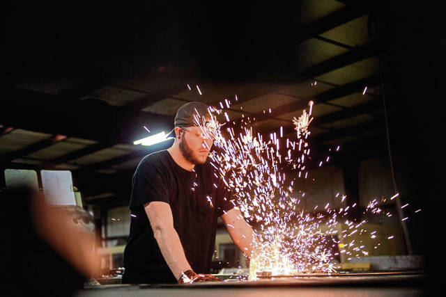 Sparks fly as Ryan Cooley, 24, of Delmont, welds together a window screen frame at FlexScreen in Murrysville.