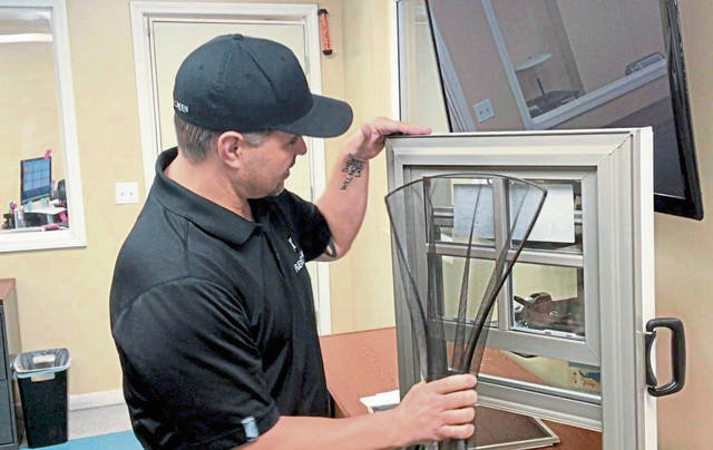 FlexScreen President Joe Altieri shows the ease of installing one of his company's flexible window screens.
